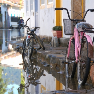 Bicycles parked by the kerb in Paraty, Brazil. The streets are flooding due to a very high tide coming in.